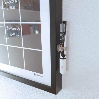 Pennhållare på ramen till en planeringstavla