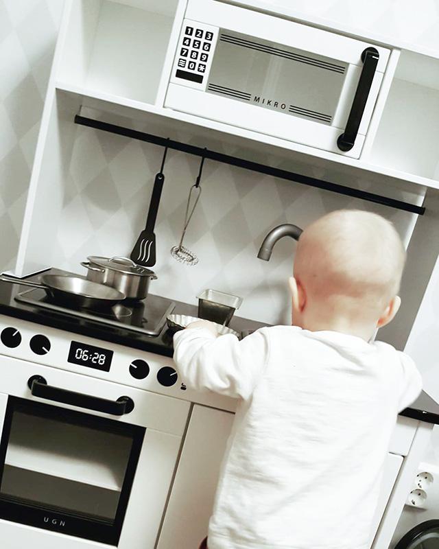 Sötaste mini-kocken stökar i sitt kök