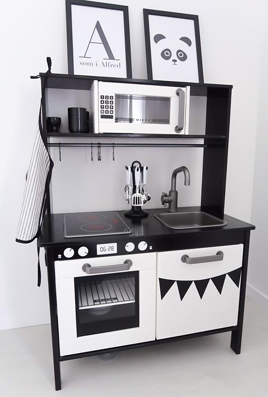 Coolaste svarta köket med vita ugnsvred och vimplar